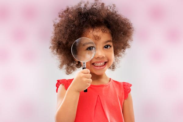 Child holding a magnifying glass. Thumbnail image for the early childhood activity Exploring Food with the 5 Senses.