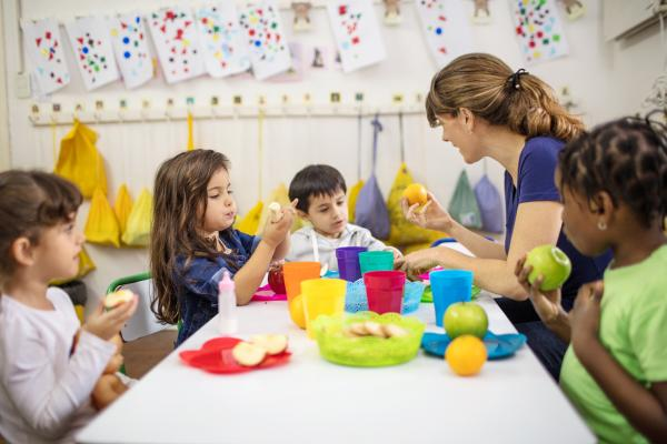 teacher sitting with children at a table eating