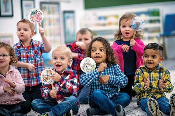 Early Childhood Educators Nursery Rhymes Activity Thumbnail – Young children singing along to a song holding stick puppets with food images