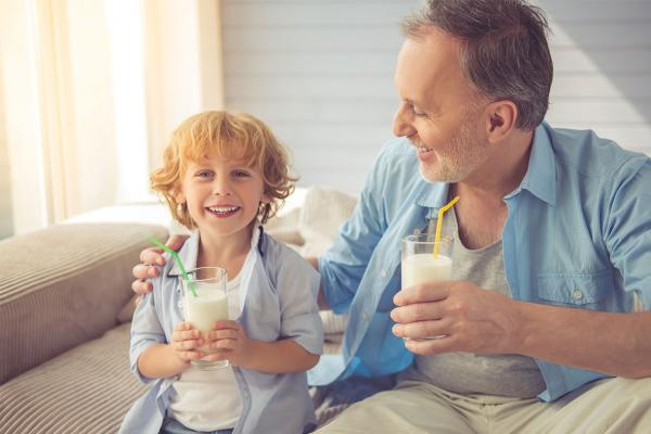 A young boy and his grandpa each drinking a glass of milk