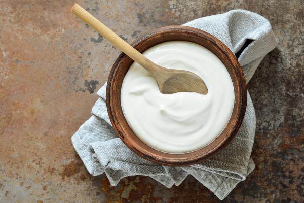 Yogurt in wooden bowl with wooden spoon