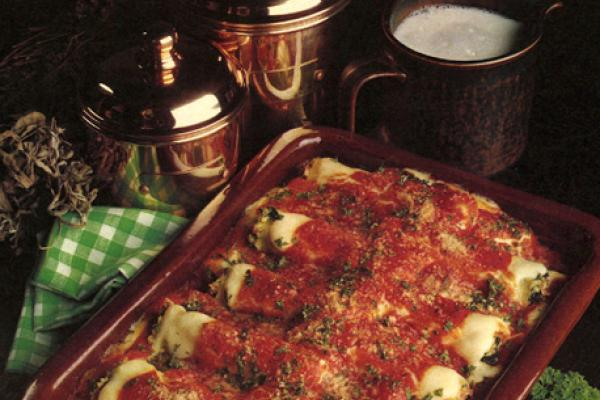 Casserole dish of Cannelloni covered in a tomato sauce