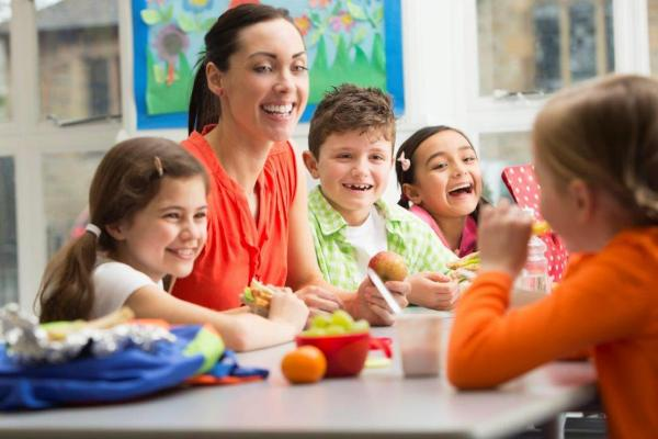 teacher sitting at a table eating with children