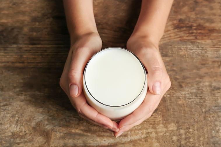 An overhead view of two hands holding a glass full of milk on a wooden table.