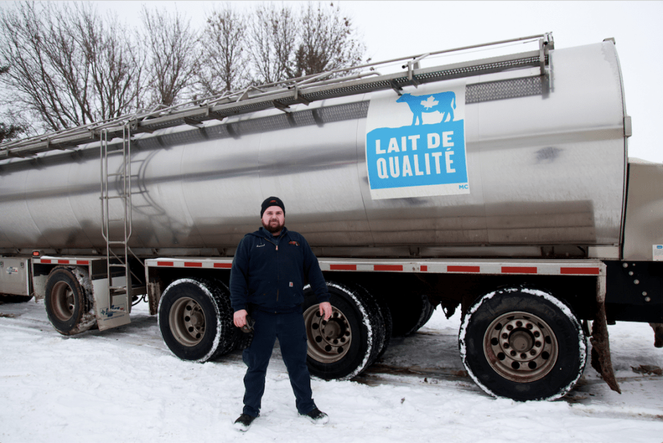 A milk truck driver in front of his DFC truck