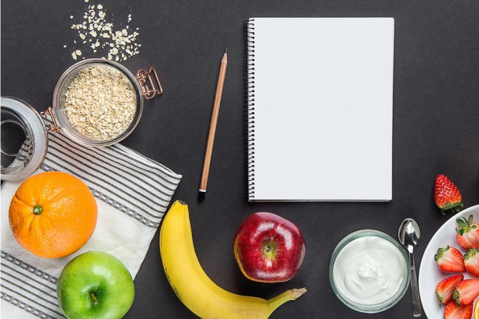 Overhead shot of booklet and pencil surrounded with fruits, oats and yogourt