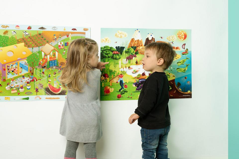 boy and girl pointing at posters on the wall