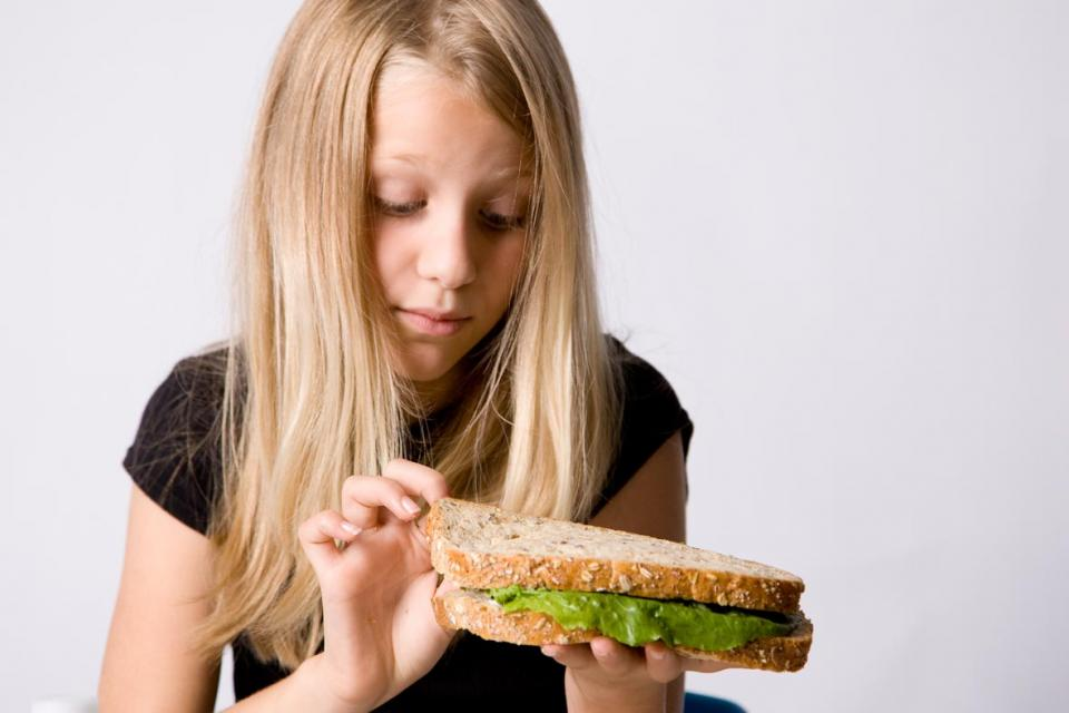 Young girl who does not want to eat her sandwich