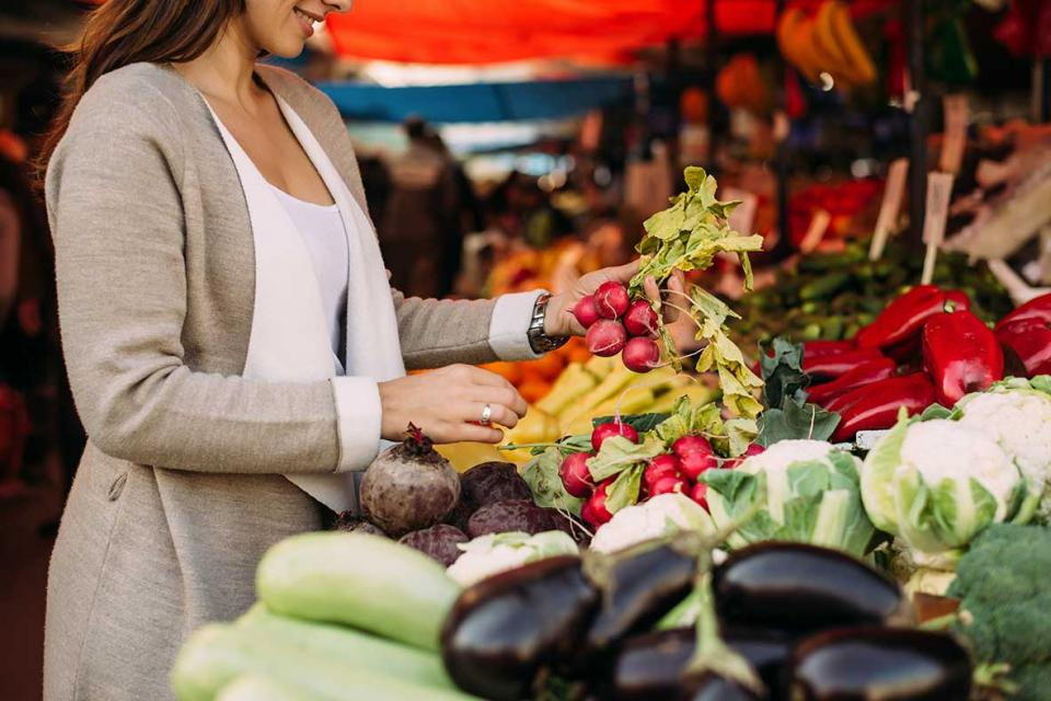 Woman buying produce at farmer's market.