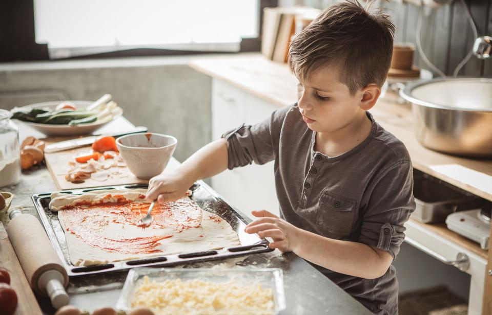 A boy spreads tomato sauce on pizza