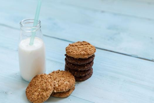 A stack of cookies next to a bottle of milk