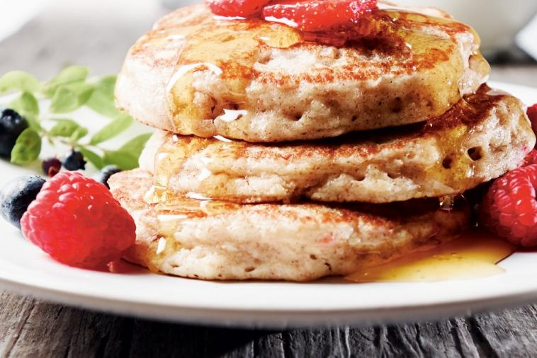 A stack of fluffy pancakes covered in syrup and berries